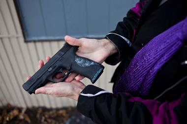 "Pam Pitlanish, of ""The Well Armed Woman"" gun club holds her ""pretty gun"" on Wednesday afternoon, Nov. 20, 2013 outside the Sentinal Protection and Investigations shooting range on Fenton road in Flint."
