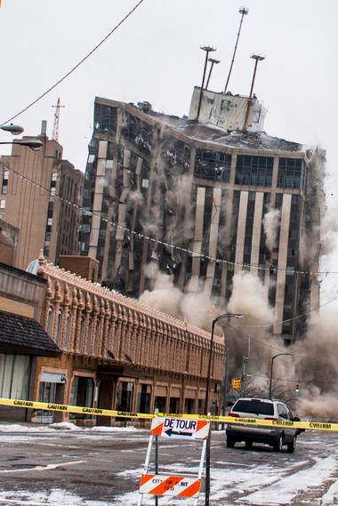 Genesee Towers falls to the ground as explosives detonate for an implosion Dec. 22, 2013, as seen from Harrison Street on Sunday, Dec. 22, 2013 in downtown Flint. Jake May | MLive.com