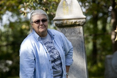 Mary Klein, of Flint, wanders around an area that marks the grave of a former Michigan School of the Death (MSD) Professor in an area where 11 orphans and former MSD students are buried without headstones to mark their burial at Glenwood Cemetery in Flint on Sept. 17, 2014. Laura McDermott | MLive.com