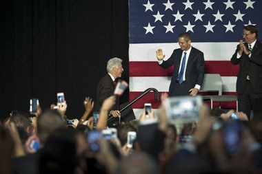 Democratic candidate for governor Mark Schauer greets former President Bill Clinton as he walks onto the stage during the rally featuring former President Bill Clinton stumping for Michigan's Democratic candidates at the Riverfront Banquet Center on Wednesday, Oct. 22, 2014 in Flint.
