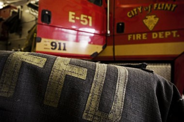 A Flint firefighter's coat sits next to a fire truck at a station on the city's east side in this Flint Journal file photo.