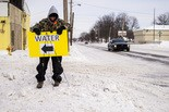 Church member and Flint resident Matthew Ferris, 37, sets a sign back up that blew over into a snowbank to signal area residents to free gallons of water on Tuesday, Feb. 3, 2015 at Lincoln Park United Methodist Church. Jake May   MLive.com