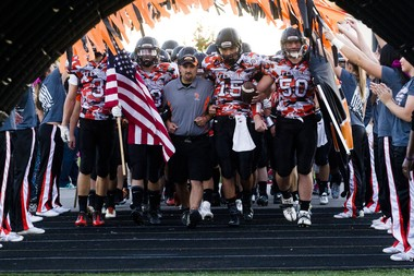"The Fenton High School football team runs through a ""Go Army"" tunnel while holding the American and Fenton flag before their game at Fenton High School on Friday evening, Oct. 11, 2013. Zack Wittman 