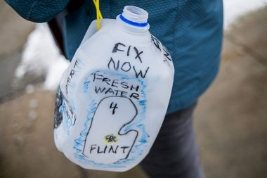 An empty one-gallon water jug is used as a sign of protest of Flint's water quality on in this 2015 Flint Journal file photo. A rally today, Aug. 31, is planned at City Hall. Flint Journal file photo