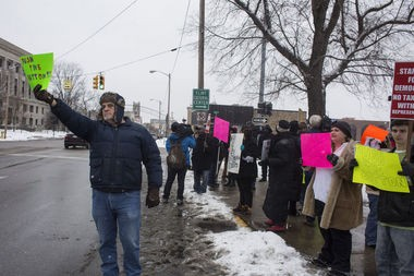 Flint resident Keith Pemberton, 66, holds up a sign toward traffic during a protest concerning water prices and quality on Wednesday, Jan. 21, 2015, outside of City Hall in downtown Flint.