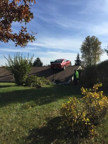 A red mustang came to rest on the peak of the rooftop of a Perry Township home after leaving eastbound I-69 Monday afternoon, Oct. 26.