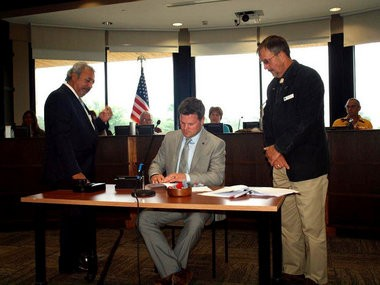 At center, David Nyberg, Director of the Office for Northern Michigan, State of Michigan, signs a sewer agreement the agreement along with Little River Band of Ottawa Indians Ogema Larry Romanelli, left, and Tribal Council Speaker Virg Johnson, right.