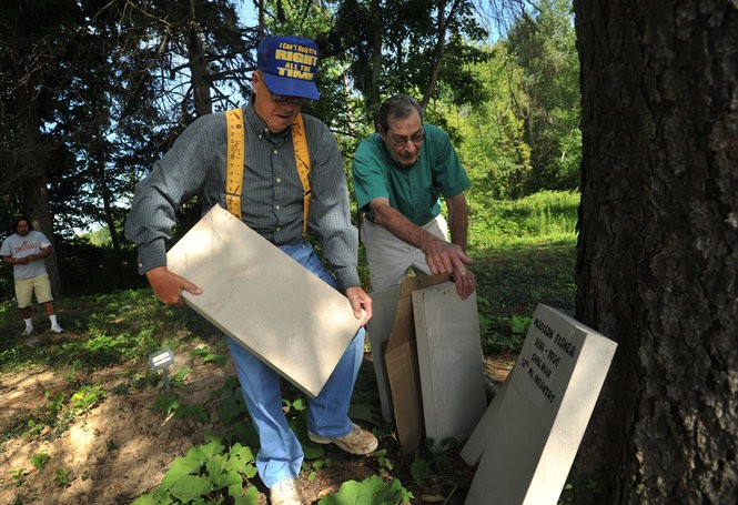 Bill Morgan (right) of Swartz Creek and Kenneth Bennett of Gaines Twp. arrange headstones that will be laid on the ground to identify the graves of Chippewa Indians at a Chippewa Indian burial ground in Swartz Creek.Oscar Durand / The Flint Journal The Flint Journal