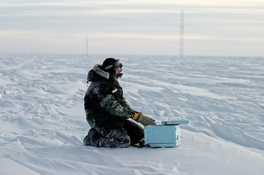 Keith Reimink films the South Pole terrain. He kept his camera and its batteries warm by heating up a lump of lead that he placed inside the foam insulating box that housed his camera.