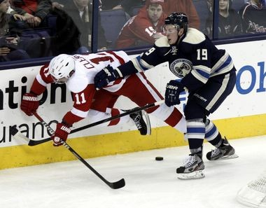 Detroit Red Wings forward Danny Cleary (left) is checked to the ice by Ryan Johansen of the Columbus Blue Jackets on Saturday.