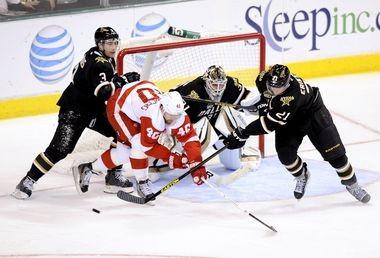Detroit Red Wings captain Henrik Zetterberg battles Stephane Robidas (3) and Loui Eriksson of the Dallas Stars for the puck.