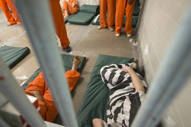 Inmates wearing a mix of orange and black-and-white striped jumpsuits are lodged in a cell at the Saginaw County Jail.