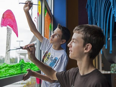 Matthew Wolfgram and Devon Frost (middle) paint on a window at the Mid-Michigan Children's Museum, 315 West Genesee in Saginaw, Tuesday, Oct. 21, 2014. A group of White Pine Middle schoolers painted the windows in the cafeteria and waterworks area. The theme was Fantasy Landscapes.