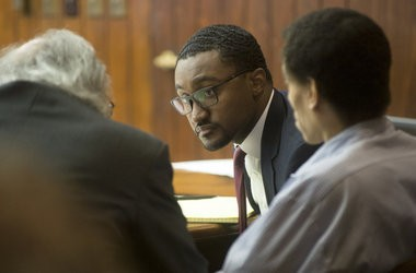 Birl L. Hill, right, and his defense attorneys James Piazza, left, and Alan Crawford, center, confer during Hill's trial in front of Saginaw County Circuit Judge Darnell Jackson on Dec. 12, 2014.