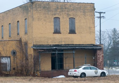 A Saginaw Police Department car sits next to a body that was found behind a building in an empty lot near the intersection of S. Fourth and Walnut in Saginaw on Tuesday, Jan. 29.