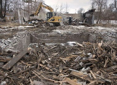 A crew from Rodney Woods Builders demolishes a house and a large garage at 1715 Annesley in Saginaw, March 20, 2014. The city of Saginaw is using a using an $11.2 million federal grant to raze hundreds of houses to reduce blight.