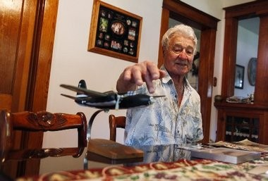 Neil Barris | Mlive.com WWII veteran Edward Moll, 89, points to a replica A-20 plane that he flew in the war at his home in Saginaw Township, Sept. 3, 2014. Moll served in the Army from 1943-1945.
