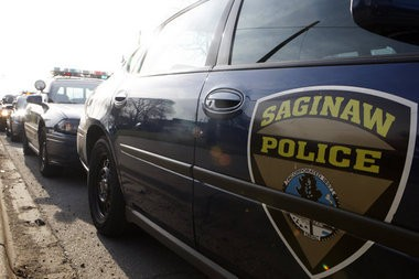 Saginaw Police Department cars are parked along a city street.