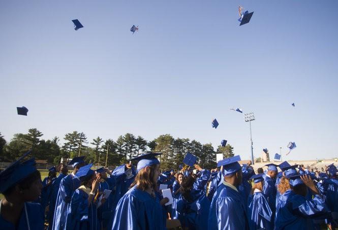 (2014) Arthur Hill graduates throw their caps in the air.