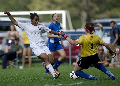 Ashton Brooks (#18) from Midland Dow and Emily Fisher (#1) from Midland High School fight for the ball during a game Monday, May 18, 2015 at Dow High School in Midland.