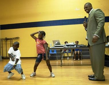 """Former Saginaw High football star LaMarr Woodley enjoys watching students dance at his """"First Impressions"""" event, which provided backpacks, haircuts and school supplies to Saginaw students."""