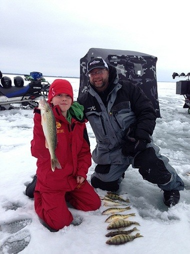 Logan Locke, 11, of Muskegon poses with a walleye and several perch he caught at Mark Martin's Ice Fishing Vacation School.