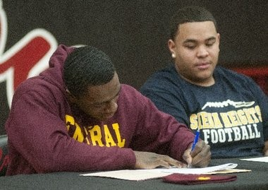 Carrollton High School football player Derrick Nash, left, signs his National Letter of Intent to play college football as teammate Dominic Williams waits his turn during a ceremony in the school gym. Nash, a running back, signed with Central Michigan University and Williams, a center, signed with Siena Heights on Feb. 6, 2013.