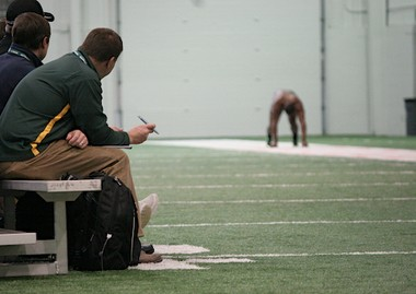NFL scouts pause as former Michigan State running back Larry Caper prepares to run the 40-yard dash.