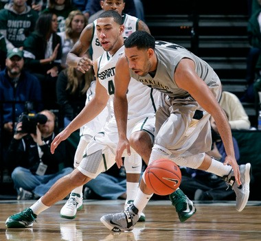 Oakland's Drew Valentine, right, and Michigan State's Denzel Valentine battle for the ball last season. The two are brothers from Lansing.