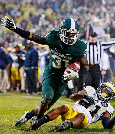 Darqueze Dennard celebrates after intercepting a pass against Michigan on November 2. Michigan State won the game, 29-6. Dennard had no scholarship offers when the Spartans came to his hometown, now he's one of the best corners in the country.