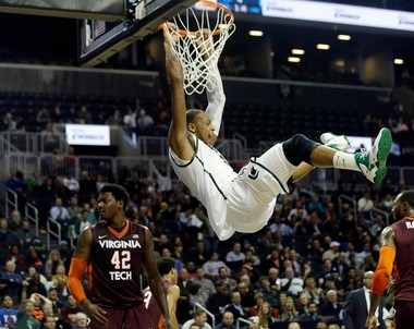 Michigan State's Adreian Payne (5) celebrates while hanging on the rim after dunking the basketball during the first half of a Coaches vs. Cancer NCAA college basketball game against the Virginia Tech, Friday, Nov. 22, 2013, in New York.