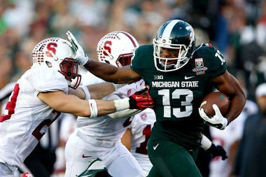 Former Michigan State receiver Bennie Fowler fights off Stanford defensive backs on a 60-yard gain in the Spartans' 24-20 victory over Stanford in the Rose Bowl on Jan. 1, 2014.