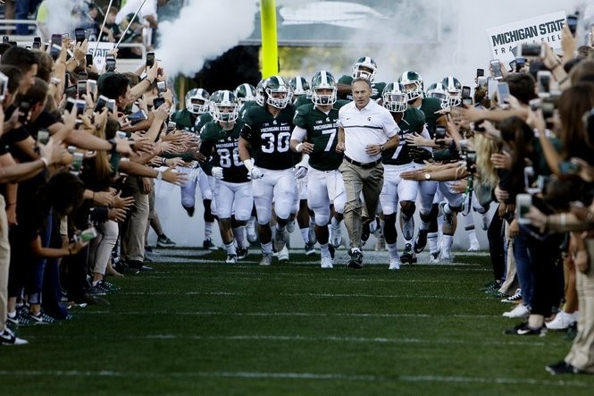 Michigan State coach Mark Dantonio leads the team onto the field before their football game against Furman at Spartan Stadium in East Lansing, on Friday, September 2, 2016. (Mike Mulholland | MLive.com) Mike Mulholland