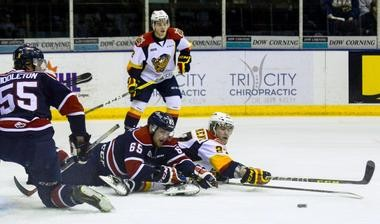 Erie Otters forward Jake Marchment (27) and Saginaw Spirit defenseman Will Petschenig (65) both reach for the puck after falling during the fourth game of the Otters' playoff series against the Saginaw Spirit at the Dow Event Center in Saginaw, Mich. on March 31, 2016. (Jake Hamilton | MLive.com File)