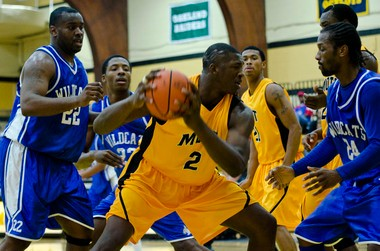 Mott freshman Coreontae DeBerry shields the ball in the first half against Wayne County on Saturday, Jan. 12, 2013 at Ballenger Field House. Mott defeated Wayne 79-67.
