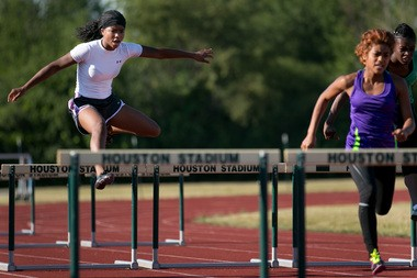Chenelle Harkless, age 15 of Northwestern, jumps midway through her 100 yard hurdles run. Flint Olympian Games track and field participants compete during the 2012 Flint Olympian Games.