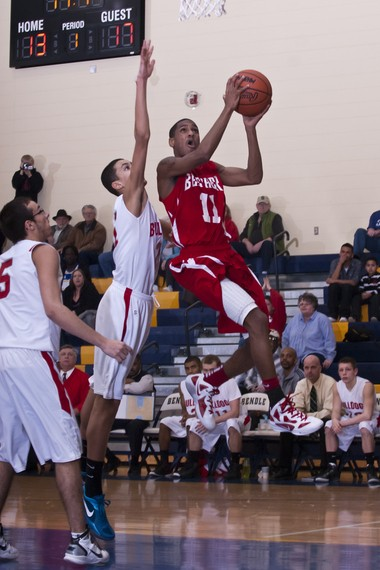 Lathan Goumas | MLive.comMarch 7, 2012 - Monte Morris(red) of Beecher High School does a layup as he is fouled by Kyle Kuzma of Bentley High School during a district semifinal game at Bendle High School in Burton on Wednesday.