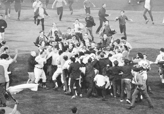 Fans surge out onto the field to surround the Detroit Tigers who came out of the dugout to greet third baseman Don Wert after his game-winning hit at Tiger Stadium that secured the AL pennant.