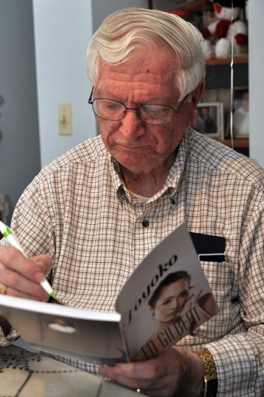 Author Ed Gilbert autographs new book.