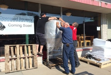 Moving a 600-pound fermentation tank into its new home in downtown Wayland are, from left, Openroad Brewery owner Bruce Patrick; Ed Haveman of West Michigan Forklift; and Awesome Chocolates owner Henry Klok.