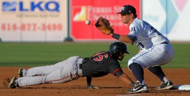 Lansing Lugnuts runner Dwight Smith Jr. dives back into first base while West Michigan Whitecaps first baseman Dean Green fields the throw.