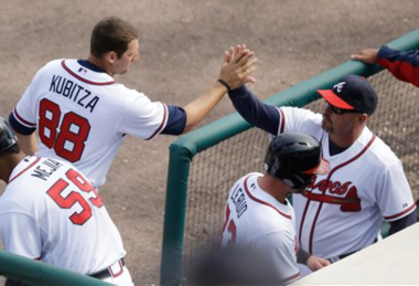 Atlanta Braves' Kyle Kubitza and Steven Lerud are greeted by manager Fredi Gonzalez as they enter the dugout during a spring training game on March 26, 2014.