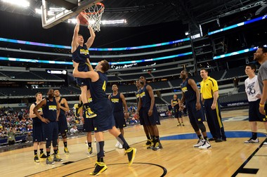 Michigan's Mitch McGary lifts point guard Spike Albrecht for a dunk to conclude Thursday's practice at Cowboys Stadium. The Wolverines say they're feeling loose heading into Friday's pressure-packed game against top-seeded Kansas.