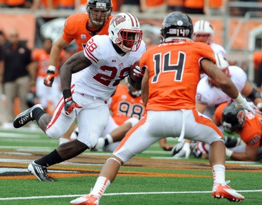 Oregon State's Jordan Poyer, right, tries to tackle Wisconsin's Montee Ball during a game last season. Michigan's quarterbacks will wear jerseys like Poyer's during Saturday's spring game.