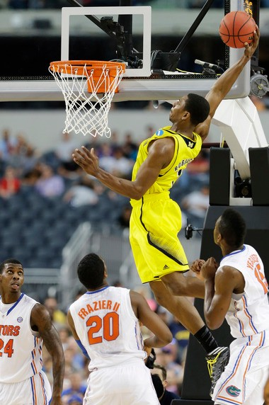 Michigan's Glenn Robinson III (1) dunks as Florida's Michael Frazier II (20), Casey Prather (24) and Will Yeguete (15) look on during the second half of Michigan's 79-59 win in the regional finals of the 2013 NCAA tournament on March 31, 2013, in Arlington, Texas.