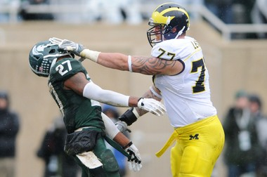 Michigan offensive linesman Taylor Lewan draws a personal foul as he roughs up Michigan State safety Kurtis Drummond during the first half at Spartan Stadium on Saturday, November 2, 2013.