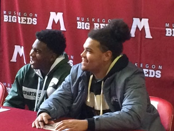 Muskegon teammates La'Darius Jefferson, left, and Antwan Reed share a laugh during a signing event Wednesday at Muskegon High School. Jefferson signed with Michigan State and Reed signed with Western Michigan.