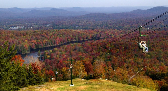 With the fall leaves at peak in the Adirondack park, the view of people riding the chair lift to the top of McCauley Mountain in Old Forge. Photo was taken from the top of McCauley Mountain.