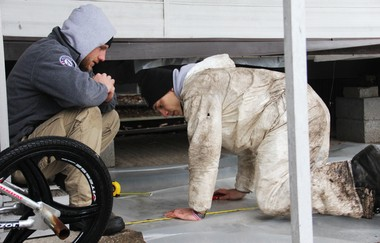 Americorps NCCC members Casey McLellan and Joey Thompson measure and cut sheets of plastic to protect insulation installed beneath mobile homes in Moonachie on January 16, 2012.