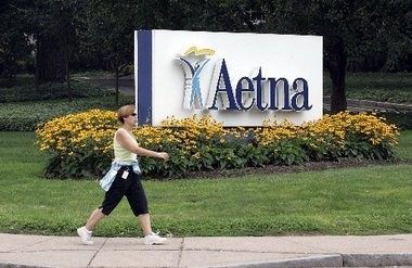 In this July 31, 2008 file photo, a woman strides past the Hartford, Conn., headquarters of Aetna. The health insurance company is withdrawing from the health exchange.